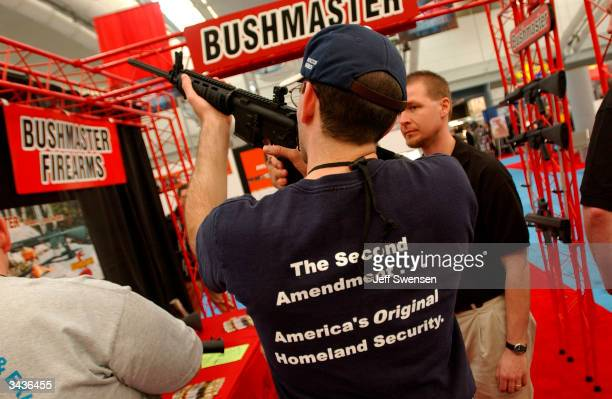 A conventioneer inspects an assault rifle on display at the 133rd National Rifle Association National Convention at the David L Lawrence Convention...