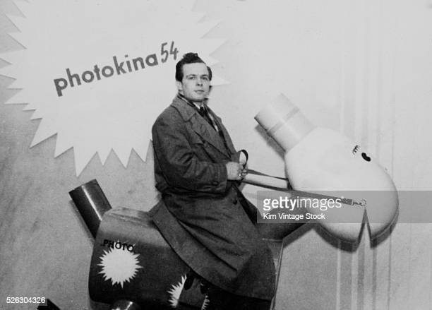 A conventioneer rides a mockup of a photographic strobe made to look like a horse at Photokina 1954 Photokina is the worlds largest trade show for...