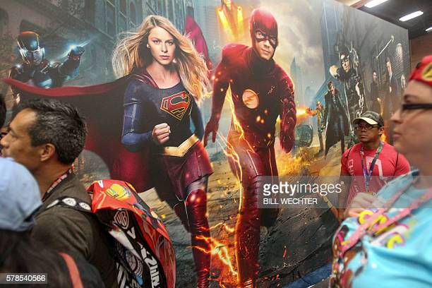Conventiongoers saunter by as Supergirl and The Flash jump pff a mural during ComicCon International 2016 in San Diego California on July 21 2016 /...