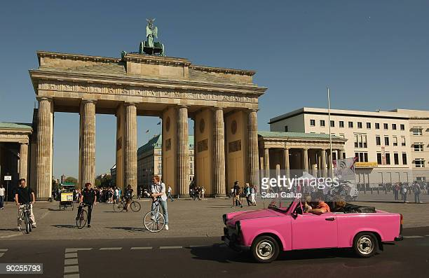 A converted pink Trabant car operated by Trabi Safari drives past the Brandenburg Gate on September 1 2009 in Berlin Germany Trabi Safari takes...
