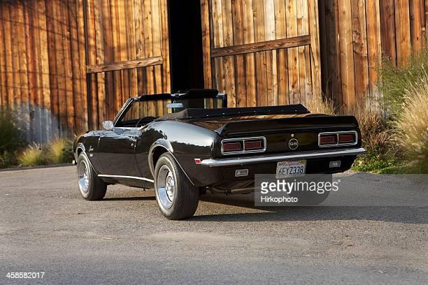 convertible camaro next to barn - camaro stock photos and pictures