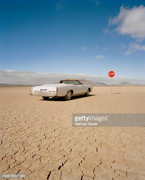 convertible car at stop sign, rear view - lake bed stock pictures, royalty-free photos & images