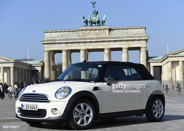 A convertible car of German carsharing company DriveNow manufactured by brand Mini stands in front of the Brandenburg Gate in Berlin on April 10...