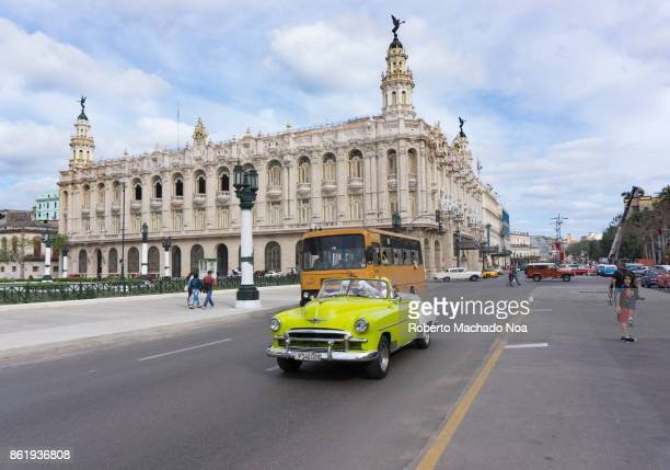 Convertible old American car on a downtown road Bus and other vehicles sharing the urban street The Alicia Alonso National Theatre in the background