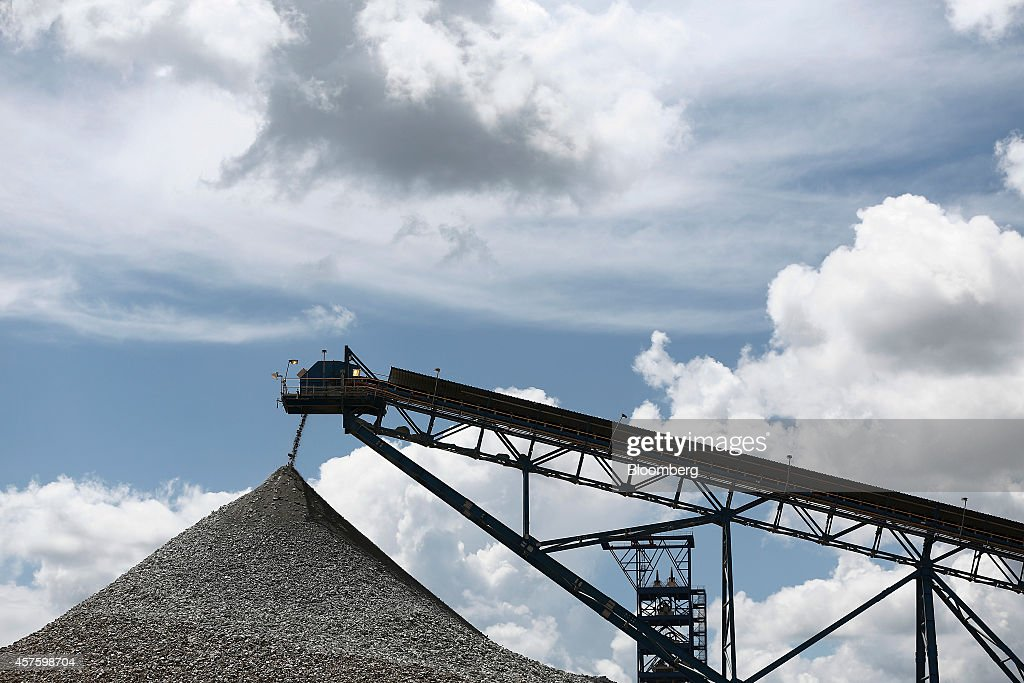 A conveyor belt deposits processed rock ore onto a dump at the