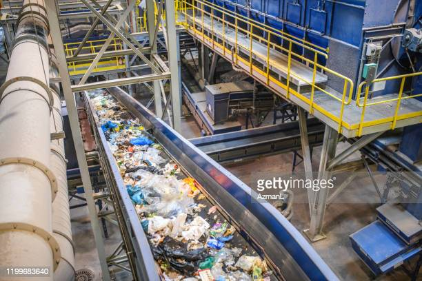 conveyor belt for recyclables in waste processing facility - rubbish stock pictures, royalty-free photos & images