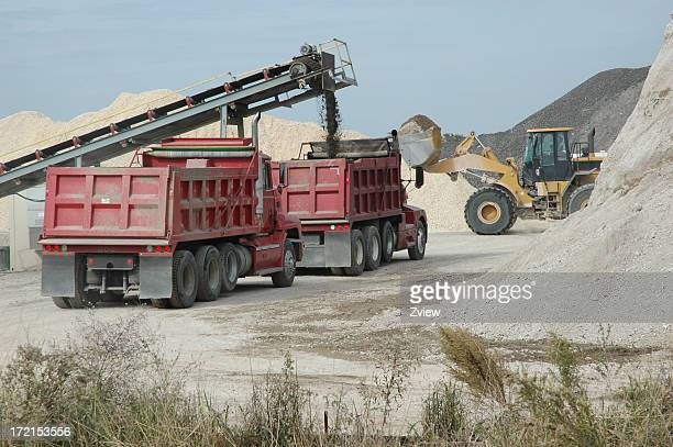 conveyor belt loading dump trucks at road construction site - dump truck stock pictures, royalty-free photos & images