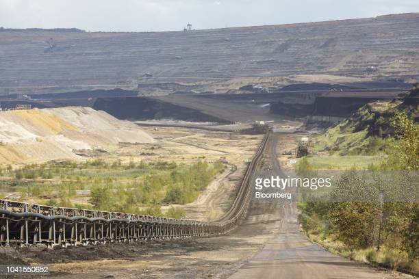 A conveyor belt runs beside a road at the open pit lignite mine operated by RWE AG in Hambach Germany on Monday Aug 13 2018 Not far from Germanys...