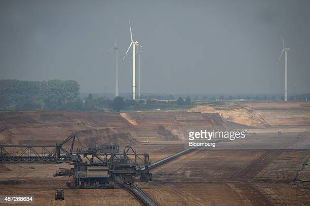 A conveyor belt runs from a giant excavator as wind turbines stand beyond at an open pit lignite mine also known as brown coal operated by RWE AG in...