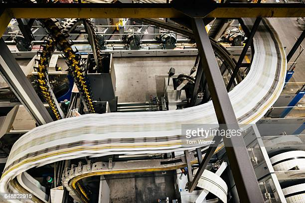 conveyor belt with newspapers in a printery - printing press stock pictures, royalty-free photos & images