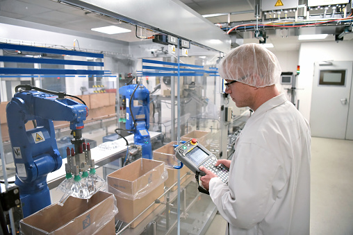 Conveyor belt worker operates a robot that transports insulin bags - modern factory for the production of medicines in the healthcare sector 980812576