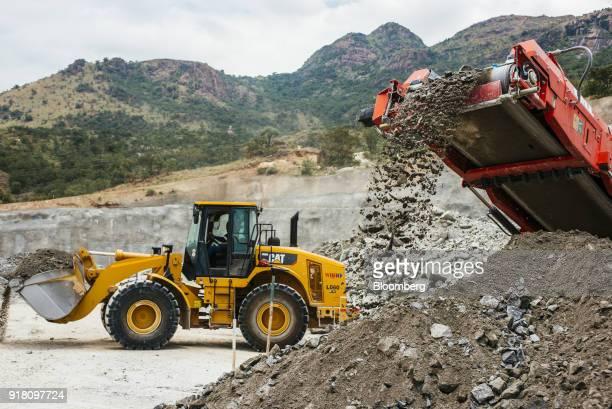 A conveyor deposits raw aluminum ore onto a stockpile as a Caterpillar Inc excavator passes at the Northam Platinum Ltd Booysendal platinum mine...
