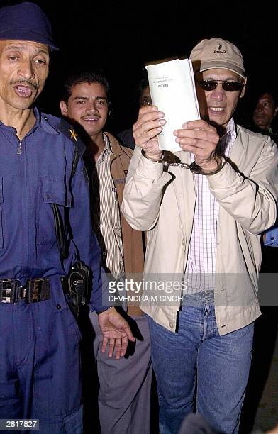 Convicted criminal Charles Sobhraj tries to hide his face while coming out of Kathmandu District Court, 20 October 2003, following a court hearing....
