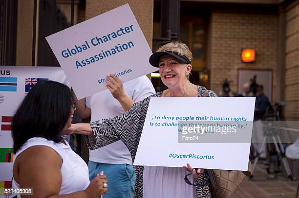 Convicted murderer Oscar Pistorius supporters carry posters outside court during his appearance for a postponement of his sentencing hearing at the...