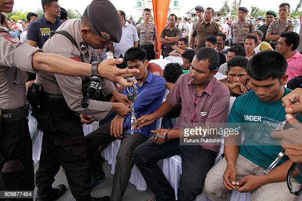 Convicted sharia offenders are led in handcuffs to the punishment ceremony at Meulabohm on February 12 2016 in West Aceh Indonesia About 32 men in...