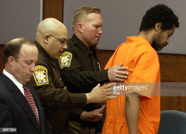 Convicted sniper John Allen Muhammad is escorted out of court by two Prince William County Sheriff deputies as his attorney Peter Greenspun stands by...