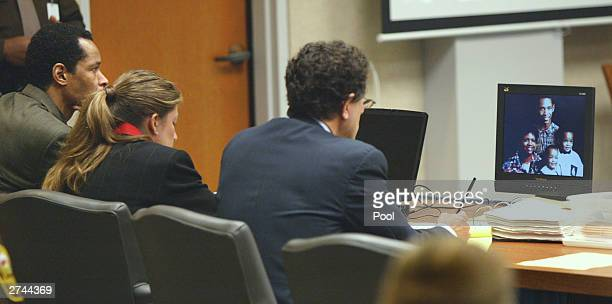 Convicted sniper mastermind John Allen Muhammad and attorneys Christie Leary and Jonathan Shapiro look at an image of Muhammad's family on a computer...