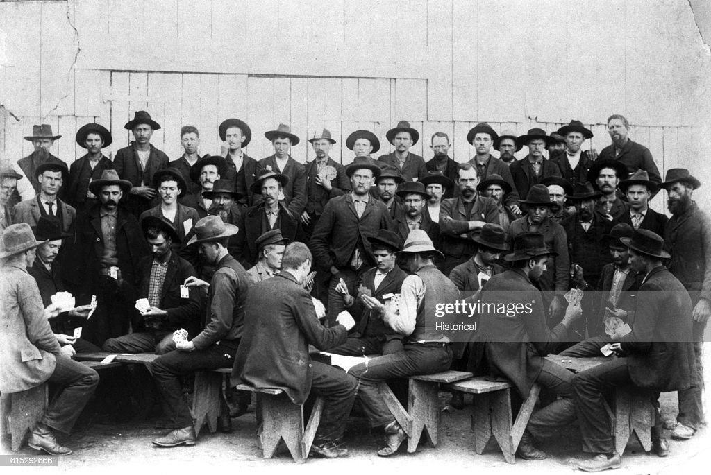 Convicts play cards in a prison courtyard in Georgia, ca  1900s