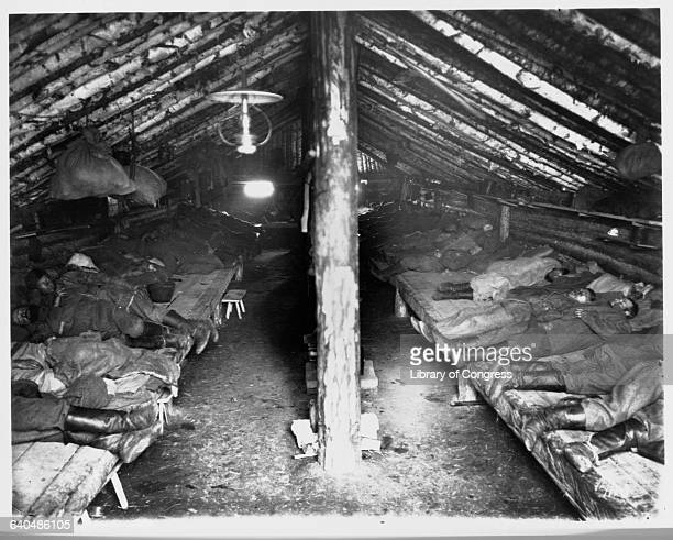 Convicts sleep on wooden benches inside crudely constructed barracks in the Khabarovsk region of Russia 1895