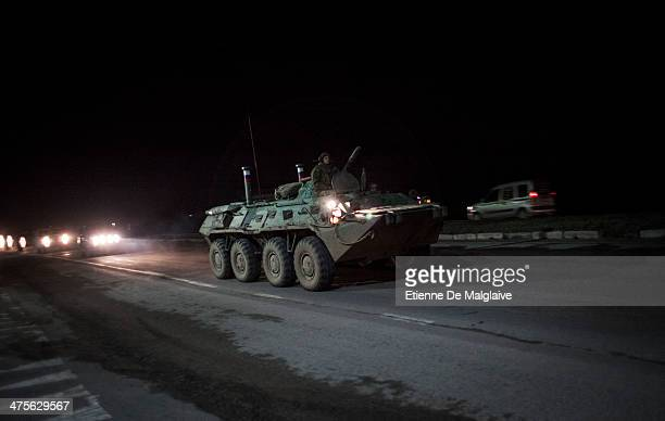 Convoy of 20 Russian armoured personnel carriers and trucks full of troops pictured in the evening 3km from Simferopol of Crimea where they are...