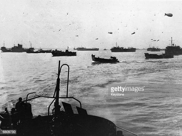 Landing craft protected by barrage balloons make their way over to France