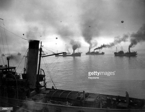 Convoy of coasters sets out at dawn under the protection of escort ships and barrage balloons against air attacks
