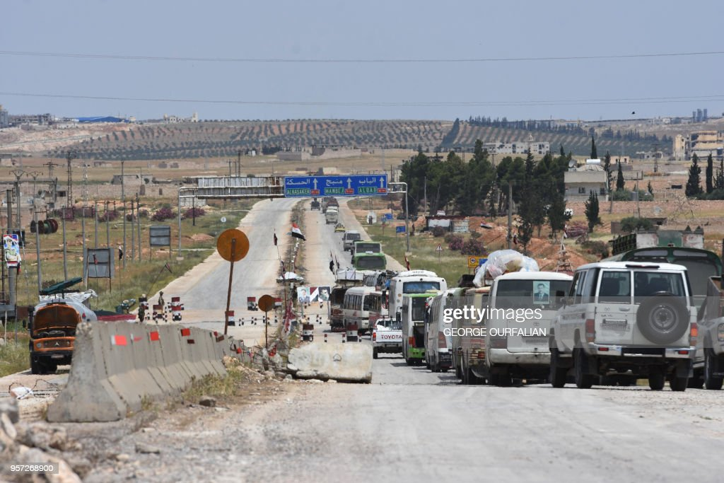 A convoy of evacuated opposition fighters from Yalda, Beit Sahem and Bebla arrive at the entrance of Aleppo on their way to al-Bab-Jarablous crossing north of Damascus on May 11, 2018.