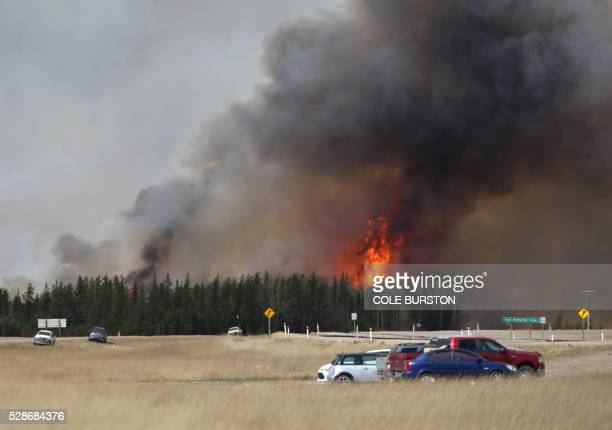A convoy of evacuees drives south as flames and smoke rises along the highway near near Fort McMurray Alberta on May 6 2016 Canadian police led...