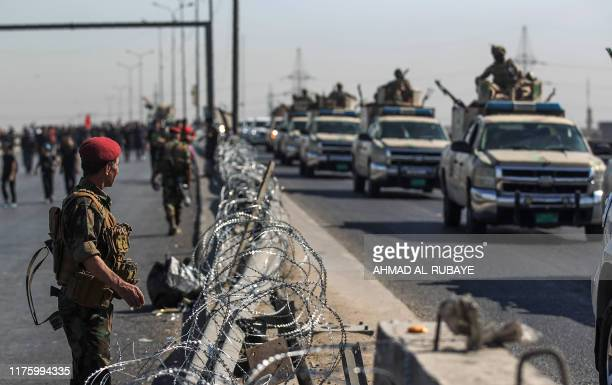 A convoy of Iraqi soldiers patrols on a road as Shiite Muslim pilgrims take part in a procession from Baghdad to the shrine of Imam Hussein in...