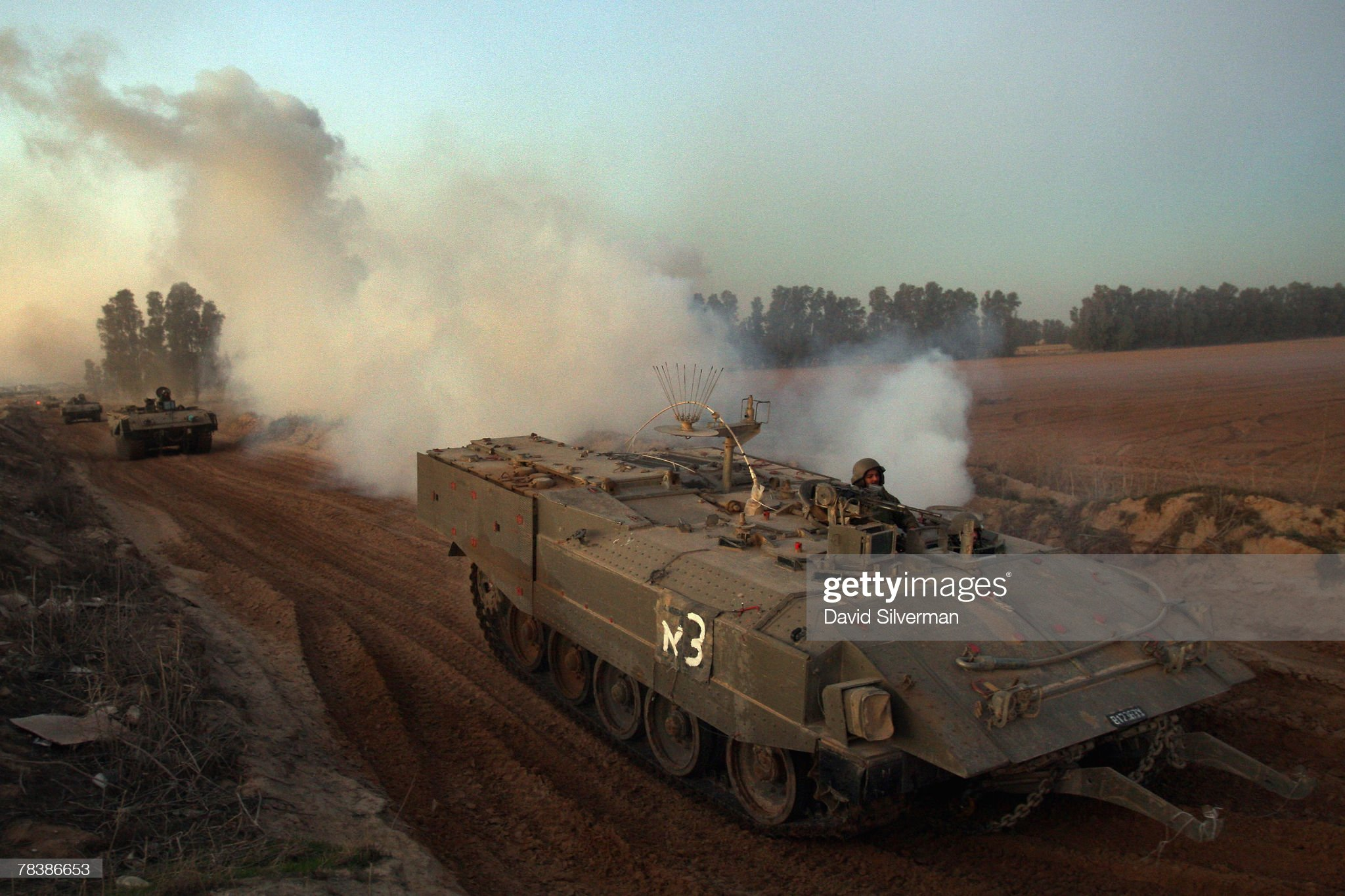 convoy-of-israeli-armoured-vehicles-churns-up-dust-and-smoke-as-it-picture-id78386653?s=2048x2048