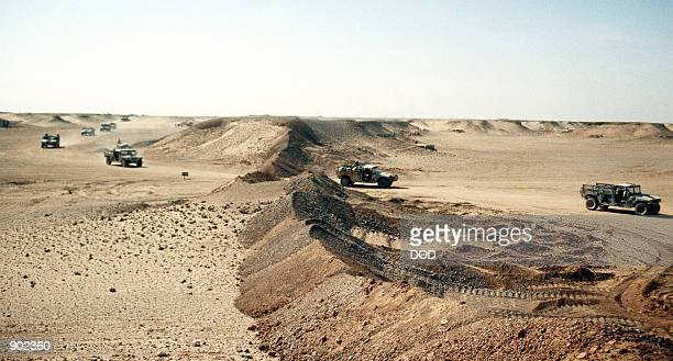 A convoy of M998 highmobility multipurpose wheeled vehicles drives past a berm as the 4th Battalion 2nd Brigade move their camp near the border of...