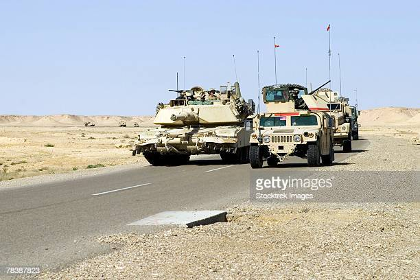 a convoy of military vehicles travel along a road in iraq. - m1 abrams stock pictures, royalty-free photos & images