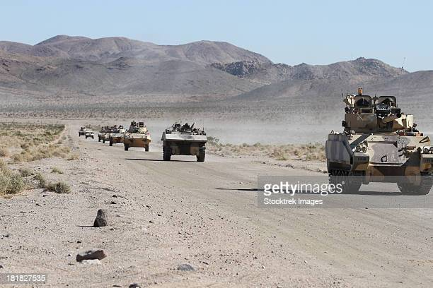 convoy of military vehicles traveling in fort irwin, california. - military convoy stock photos and pictures