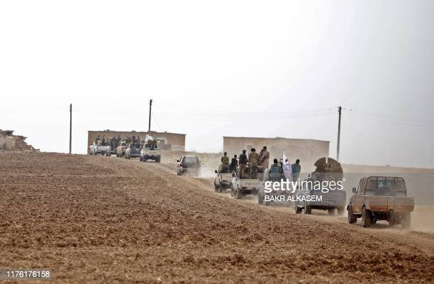 Convoy of pickup trucks transports Turkey-backed Syrian fighters on the road between the Syrian towns of Tal Abyad and Kobane on the Turkish border...