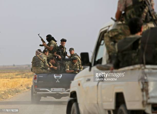 A convoy of pickup trucks transports Turkeybacked Syrian fighters on the road between the Syrian towns of Tal Abyad and Kobane on the Turkish border...