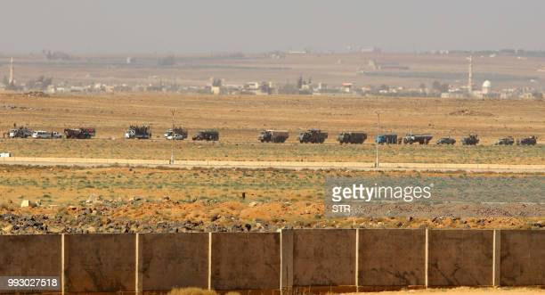 A convoy of Syrian military vehicles can be seen from the Jordanian Mafraq governate at the Nassib border between the two countries on June 7 2018...