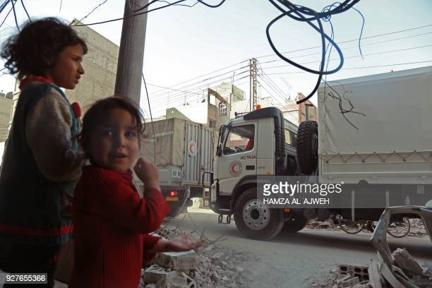 A convoy of Syrian Red Crescent trucks arrives in Douma in the Syrian rebel enclave of Eastern Ghouta on March 5 2018 on the outskirts of Damascus An...