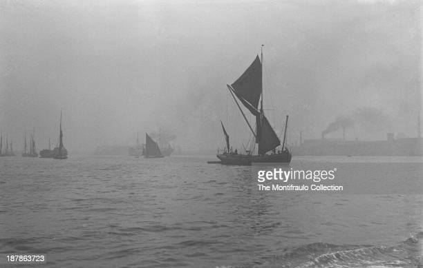 A convoy of Thames barges sailing on a mistcovered River Thames with industrial buildings in the background London England circa 1922