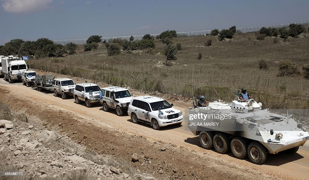 A convoy of United Nations Disengagement Observer Force (UNDOF) vehicles is seen as it leaves the Syrian side of the Golan Heights into the Israeli-occupied side of the strategic plateau, on September 15, 2014. Troops of the UNDOF were withdrawing from the Syrian part of the Golan Heights due to security reasons. The UNDOF is monitoring a 1974 ceasefire agreement between Israel and Syria on the Golan Heights.