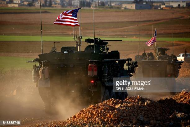 Convoy of US forces armoured vehicles drives near the village of Yalanli, on the western outskirts of the northern Syrian city of Manbij, on March 5,...