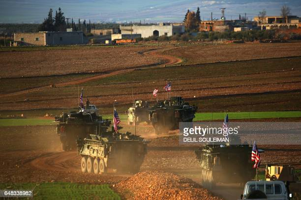 TOPSHOT A convoy of US forces armoured vehicles drives near the village of Yalanli on the western outskirts of the northern Syrian city of Manbij on...