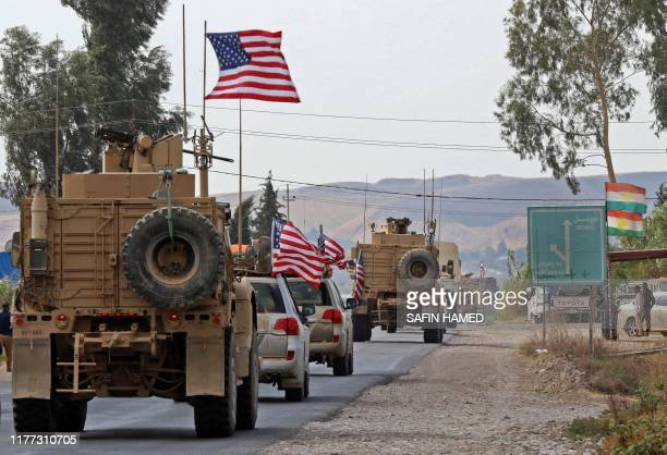 Convoy of US military vehicles arrives near the Iraqi Kurdish town of Bardarash in the Dohuk governorate after withdrawing from northern Syria on...