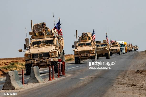 Convoy of US military vehicles, arriving from northern Iraq, drives along a road in the countryside of Syria's northeastern city of Qamishli on...