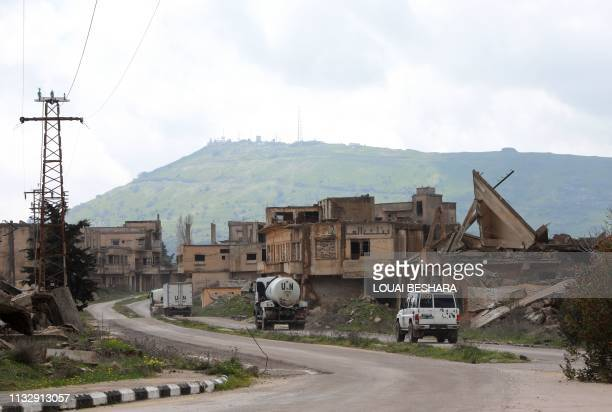 A convoy of vehicles of the United Nation drive through damaged buildings in the Syrian town of Quneitra in the Golan Heights on March 26 2019 US...
