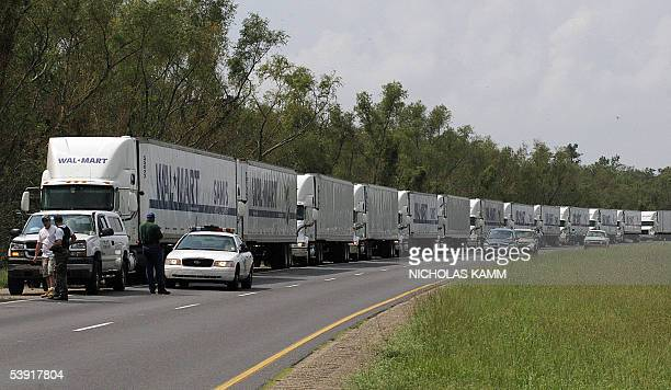 A convoy of WalMart trucks with supplies is guarded by police as they wait to entered the battered city of New Orleans near Raceland some 30 miles...