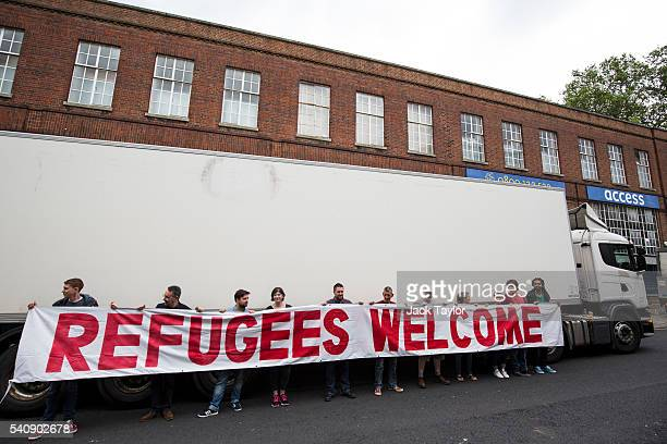 'Convoy to Calais' volunteers pose with a banner which reads 'Refugees Welcome' in front of a truck which will deliver aid to refugees and migrants...