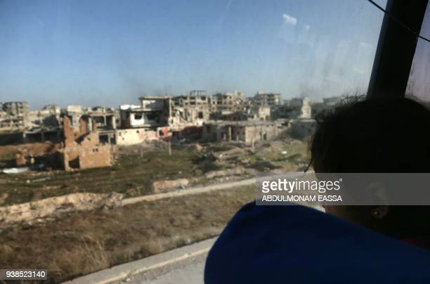 TOPSHOT A convoy transporting Syrian civilians and rebel fighters drives past destroyed buildings in Arbin in Eastern Ghouta as they are evacuated...