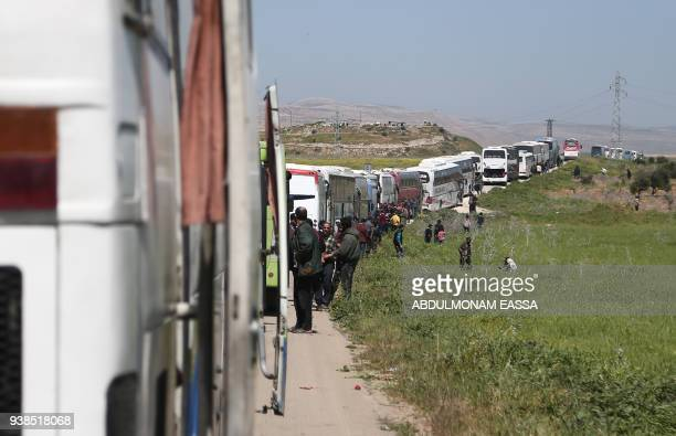 A convoy transporting Syrian civilians and rebel fighters evacuated from Eastern Ghouta waits in a governmentheld area prior to entering the village...