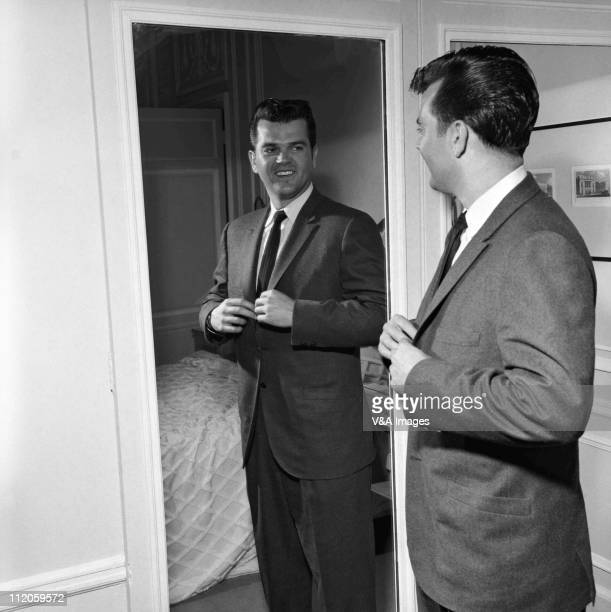 Conway Twitty, posed, fastening suit jacket in mirror, 1958.