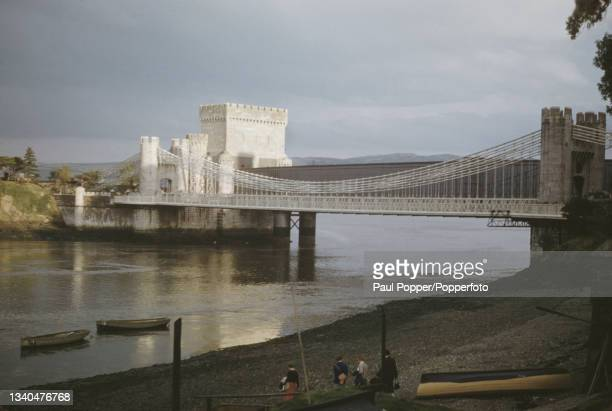 Conwy Suspension Bridge, a road bridge carrying the A55 trunk road over the River Conwy in North Wales, circa 1955. Behind the road bridge, built by...